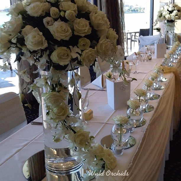The White Rose trail flowing from this traditional bouquet creates a unique cascading effect. A White Rose in each glass carries this effect to each end of the bridal table.